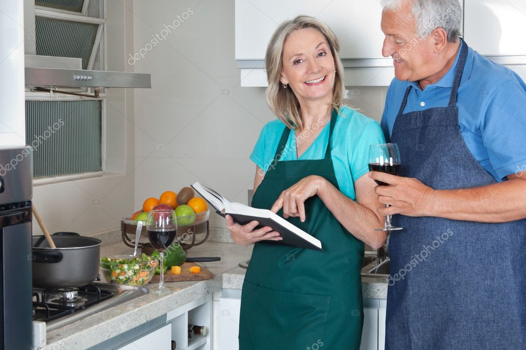 Portrait of smiling woman with recipe book and man holding wine glass in kitchen — Stock Photo #7946588