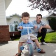 Stock Photo: Father teaching Son To Ride Tricycle