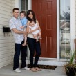 Foto Stock: Young Coupld Outside House with Kids