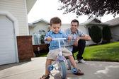 Pai ensinar o filho a andar de triciclo — Fotografia Stock
