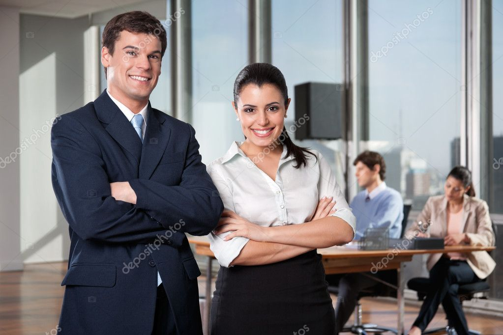 Portrait of business executives with arms crossed with colleagues working in background  Stock Photo #7954322