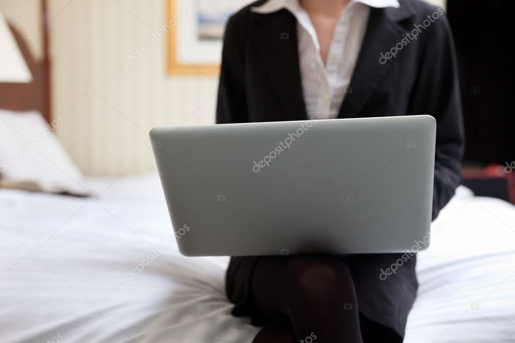 Cropped image of business woman working on laptop while sitting on bed — Stock Photo #7955398