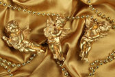 Three angels on a golden fabric — Stock Photo