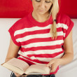 Young woman sitting on a sofa reading book — Stock Photo