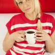 Attractive young woman drinking coffee at home — Stok fotoğraf