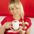 Attractive young woman drinking coffee at home — Stock Photo