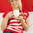 Young woman sitting on a sofa drinking coffee — ストック写真