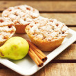 Closeup of mini pies on a plate decorated with cinnamon and a pear — Stock Photo #7001182