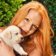 Redhead holding a cute labrador puppy - Stock Photo