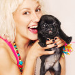 Cute blonde playing with a pug puppy — Stock Photo