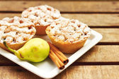 Closeup of mini pies on a plate decorated with cinnamon and a pear — Stock Photo