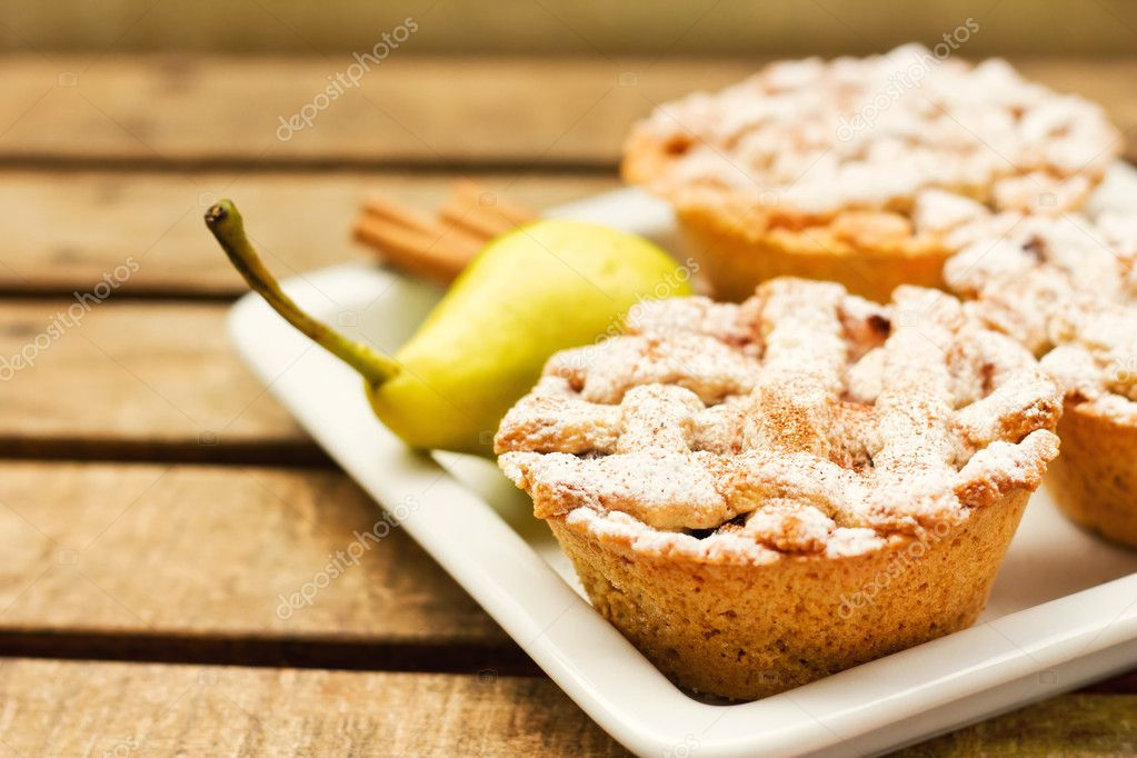 Closeup of mini pies on a plate decorated with cinnamon and a pear (shallow dof)   Stock Photo #7001216