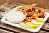 Chicken fingers served with tartar sauce and lemon slices — Stock Photo