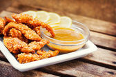 Chicken fingers served with honey-mustard dip and lemon slices — Foto de Stock