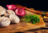 Mushrooms, onions and fresh herbs on a cutting board — Stock Photo