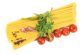 Bunch of raw spaghetti with garlic and tomato — Stock Photo