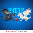 Two origami dragons and a present, 2012 year in the background — Stock Vector