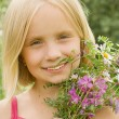 Stock Photo: Smiling girl with flowers - happiness