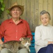 Older couple with cat sit outdoors — Stock Photo