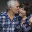 Older couple: elderly man kisses the old woman - love concept — Stock Photo