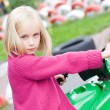 Girl in toy car - entertainment — Stock Photo