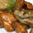Snack - chicken wings, sausages, pork ribs and cabbage - German - Stock Photo