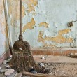 Straw broom on filthy floor — Stockfoto
