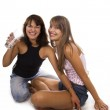 Two cheerful girls hold a glass with water — Stock Photo