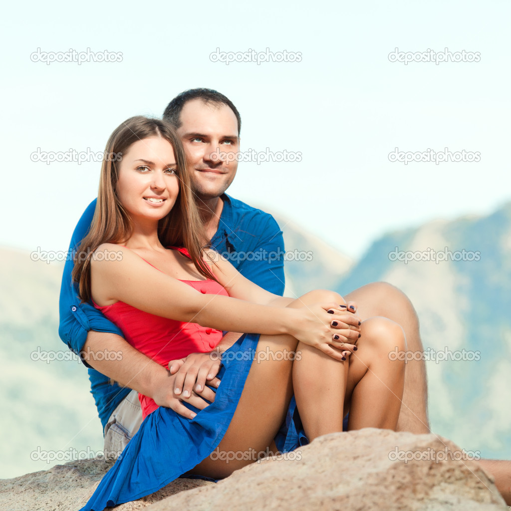 Attractive couple sitting on the cliff. Mountain on background — Stock Photo #6865657