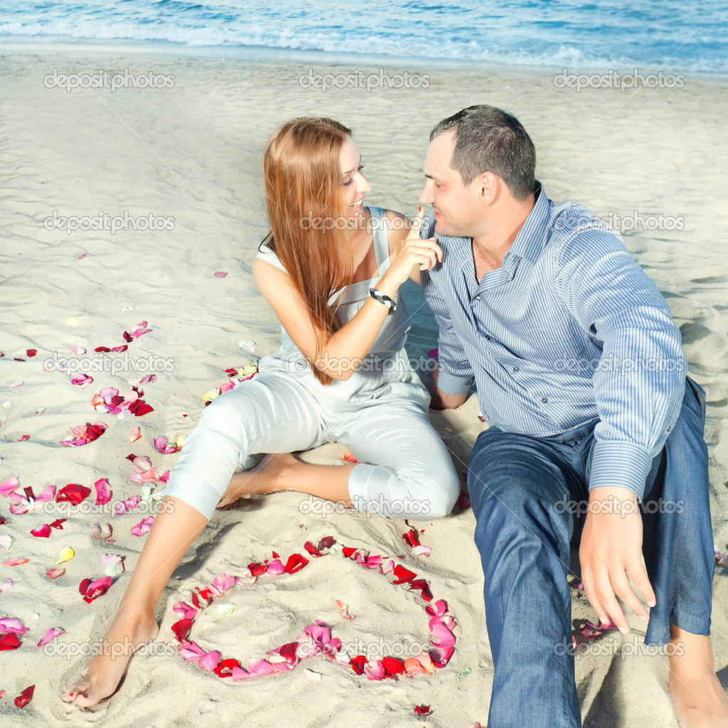 Couple on the tbeach. Yeart shape maked from petals — Stock Photo #6865789