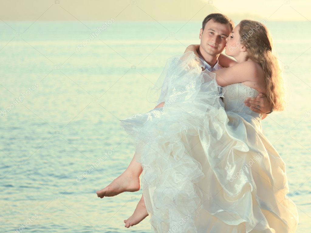 Groom holding up a his bride on the beach  Stock Photo #6865987