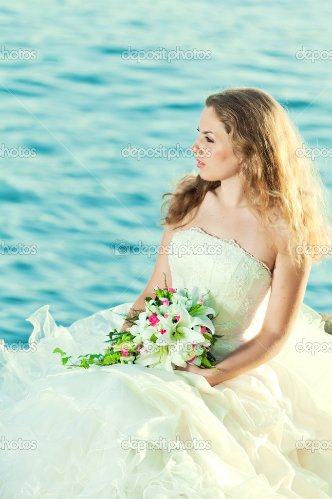 Beautiful bride sitting on a rock in a sea — Stock Photo #7238457