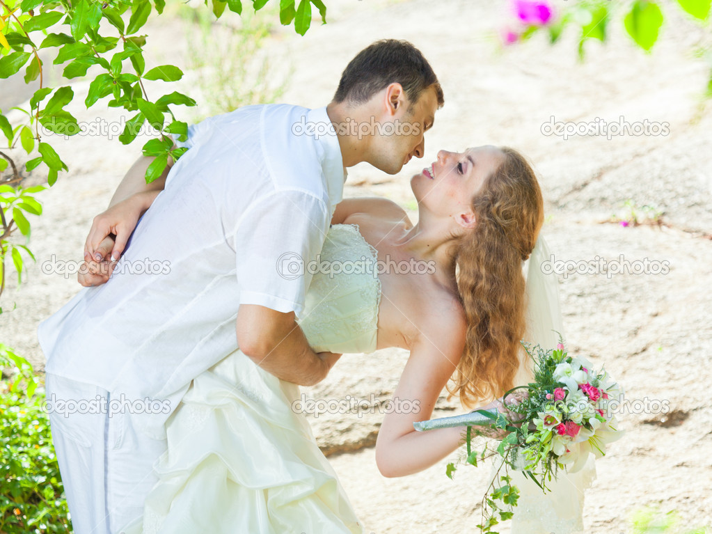 Bride and groom in a tropical garden — Zdjęcie stockowe #7238466