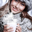 Girl blowing on hot drink dressed in winter clothing — Stock Photo