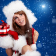 Winter portrait of a santa woman with a christmas gift — Stock Photo #6876001