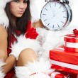 Stock Photo: Photo of Santa girl pointing at clock showing five minutes to mi