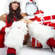Photo of Santa girl pointing at clock showing five minutes to mi - Stockfoto