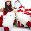 Photo of Santa girl pointing at clock showing five minutes to mi - Stock Photo