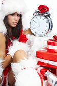 Photo of Santa girl pointing at clock showing five minutes to mi — Stock Photo