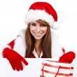 Beautiful christmas woman in santa hat holding empty board — Stock Photo #7309111