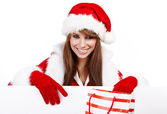 Beautiful christmas woman in santa hat holding empty board — Stock Photo