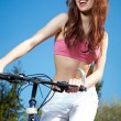 Young woman on a bicykle outdoors smiling — Стоковая фотография