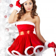 Foto de Stock  : Beautiful young woman in Santa Claus clothes holding presents ov
