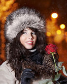 Woman in night city holding red rose. Valentine's day concept — Stock Photo