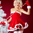 Happy cute girl in santa claus suit over red background — Stockfoto