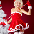 Happy cute girl in santa claus suit over red background — Stock fotografie