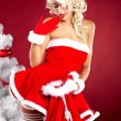 Happy cute girl in santa claus suit over red background - Stock Photo
