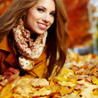 Portrait of an autumn woman lying over leaves and smiling — Stock Photo