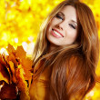 Young pretty woman at the autumn park. - Stok fotoğraf