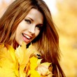 Young woman with autumn leaves in hand and fall yellow maple gar — Stock Photo